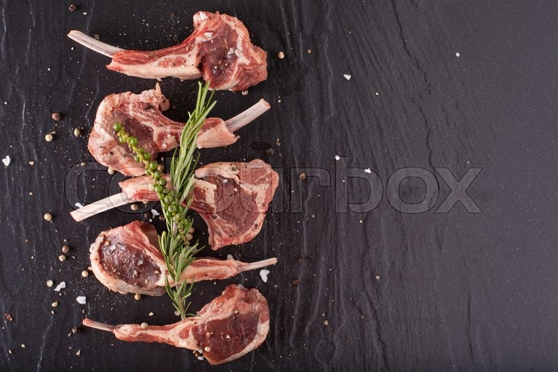Fresh lamb, fillet of red fresh rack of lamb cut in 5 pieces seasoning salt pepper and rosemary on black stone background, stock photo