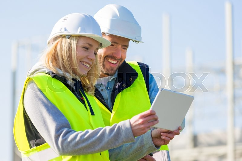 View of Two workers working outside with a tablet on a construction site, stock photo
