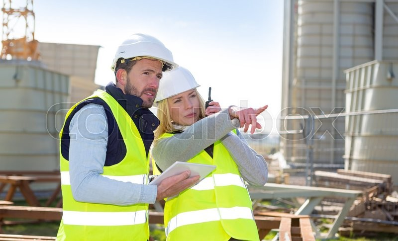 View of Two workers working outside on a construction site, stock photo