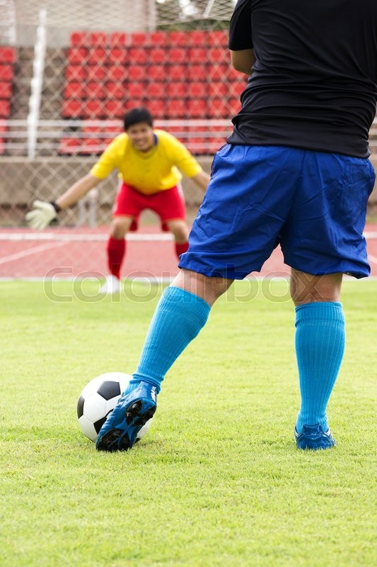 Soccer player kicking the ball for a penalty shot , stock photo
