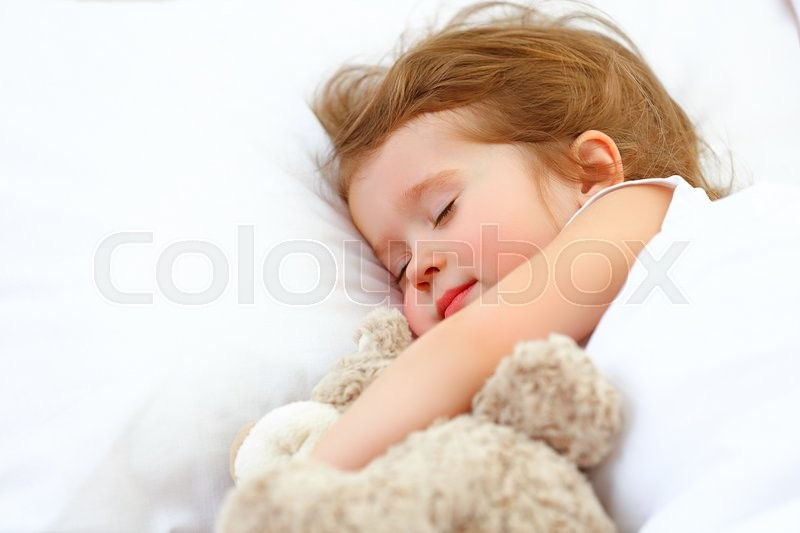Child little girl sleeps in the bed with a toy teddy bear, stock photo