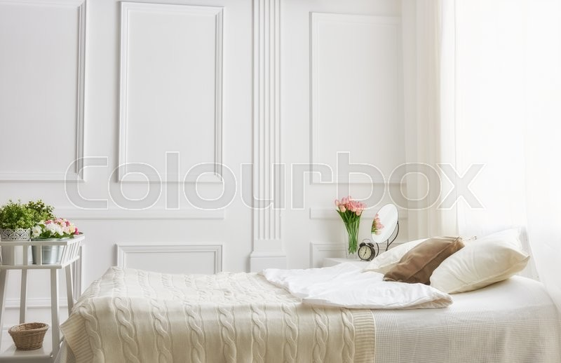 bedroom in soft light colors big comfortable double bed