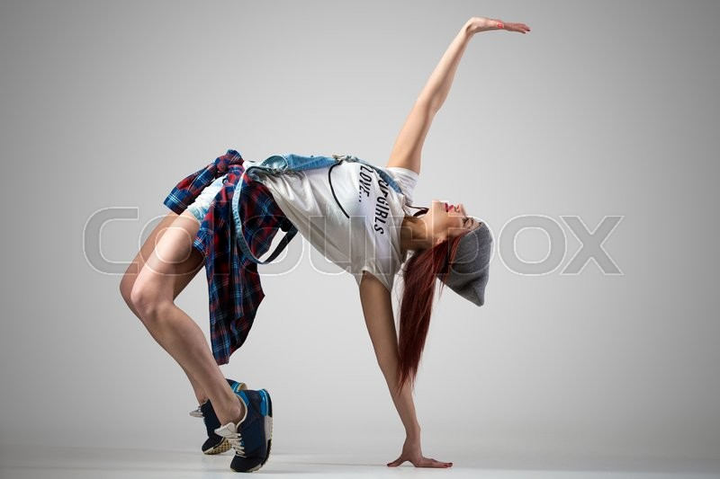 One attractive happy fit cute hipster young woman wearing casual clothing and beanie dancing. Modern style beautiful dancer girl working out, doing backbend, bridge exercise. Studio, gray background, stock photo