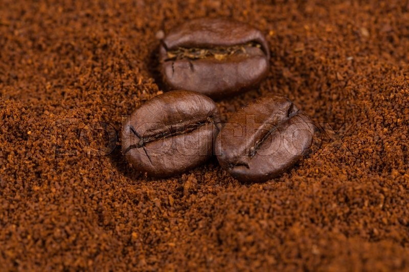 Coffee beans on heap of ground coffee close-up, stock photo