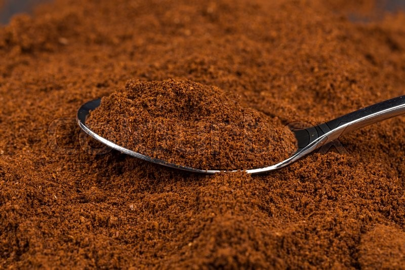 Pile of ground coffee and a metal spoon close up, stock photo