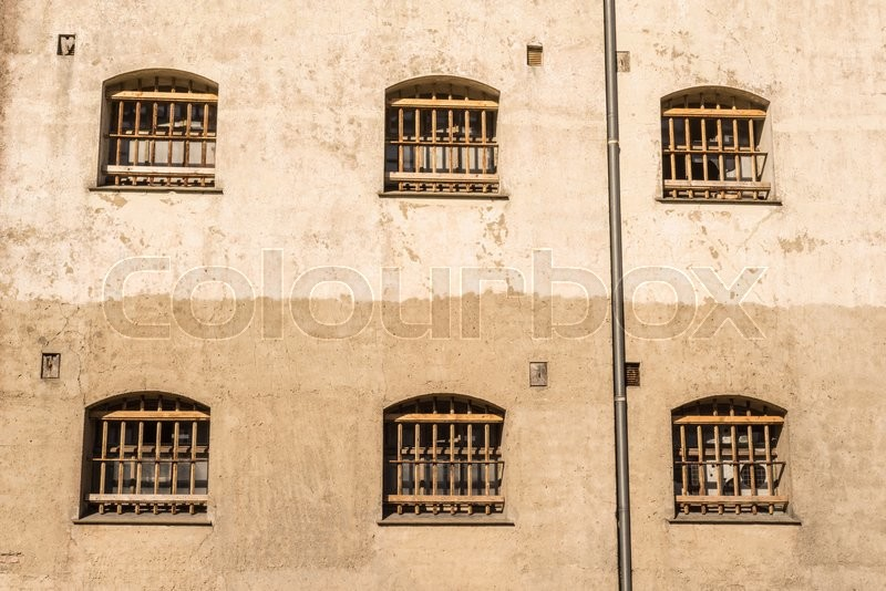 Jail wall with windows with bars on a wall, stock photo
