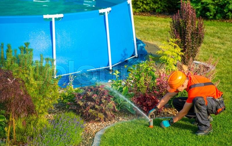 Caucasian lawn garden technician in the residential garden for Garden pool care