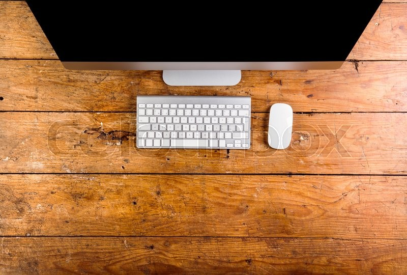 Computer, keyboard and mouse layid on wooden office desk. Flat lay. Copy space, stock photo