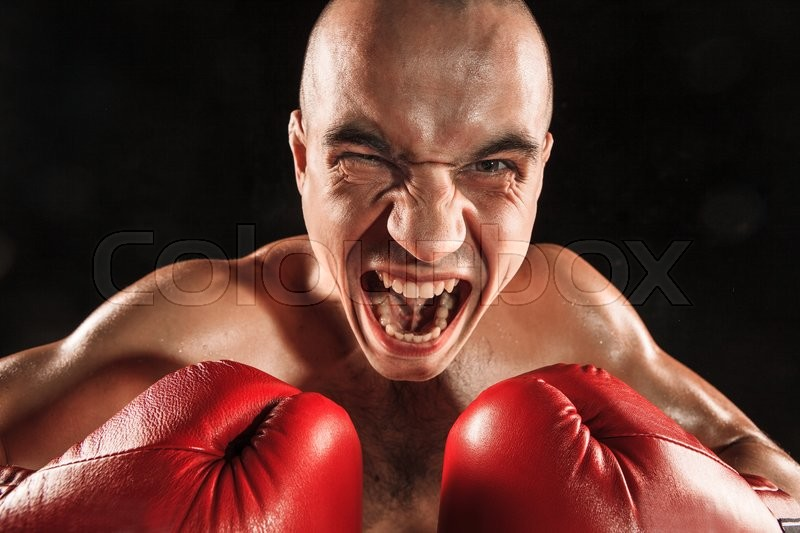 The young male athlete kickboxing on a black background with screaming face. concept fury in the fight, stock photo