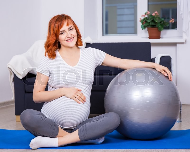 Young pretty pregnant woman exercising with fitness ball at home, stock photo