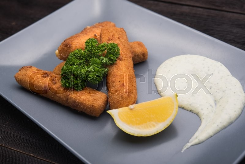 Stock image of 'cheese sticks with parsley and lemon in restaurant'