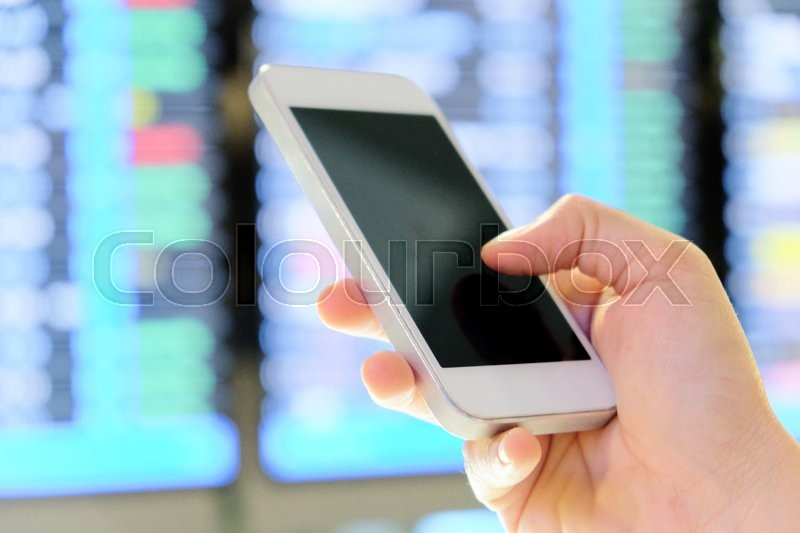 Hand holding smartphone on a flight information board in the airport background, stock photo