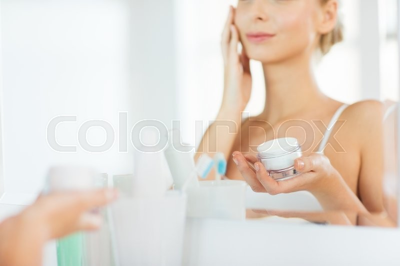 Beauty, skin care and people concept - close up of smiling young woman applying cream to face mirror reflection at home bathroom, stock photo