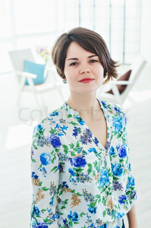 portrait of a young woman psychologist therapist in a bright office beautiful modern space with an armchair for the client consulting psychologist in the beautiful bright office