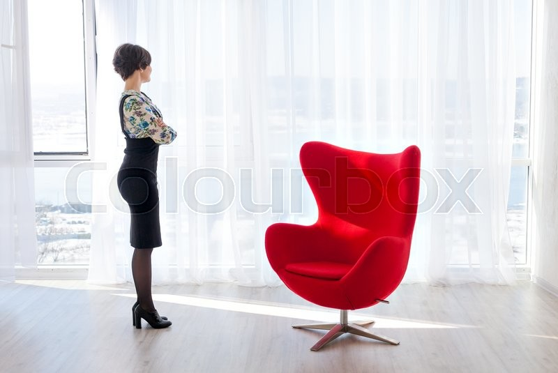 beautiful bright office. portrait of a young woman psychologist therapist in bright office beautiful modern space with red chair for the client consulting