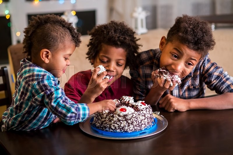 Three afro boys eating cake. Three black kids eat cake. Time for dessert. They waited for so long, stock photo