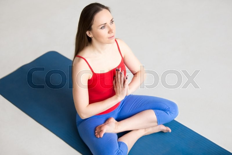Colorful Sportswear Working Out Indoors On Blue Mat Girl Sitting Meditation Session In Half Lotus Pose With Palms Namaste Top View Stock Photo