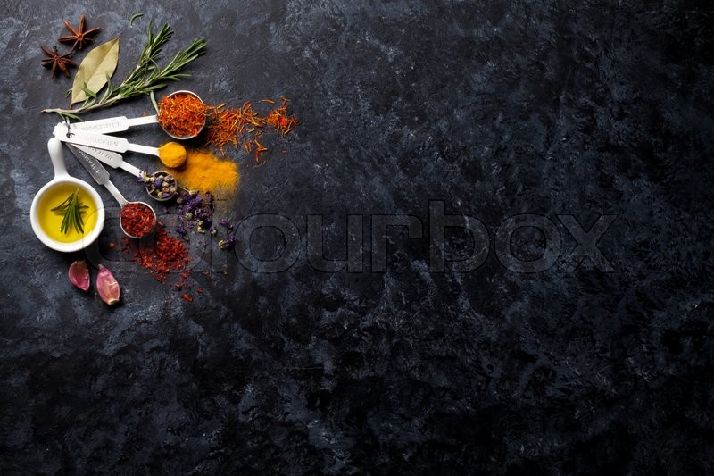 Herbs and spices over black stone background. Top view with copy space, stock photo