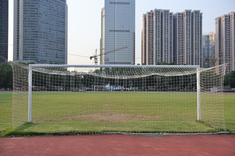 Football goal with football field and buildings as background, stock photo