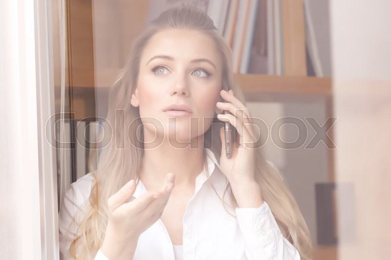 Portrait of beautiful serious business woman speaking on the phone and looking through the window, explaining something to business partner, stock photo