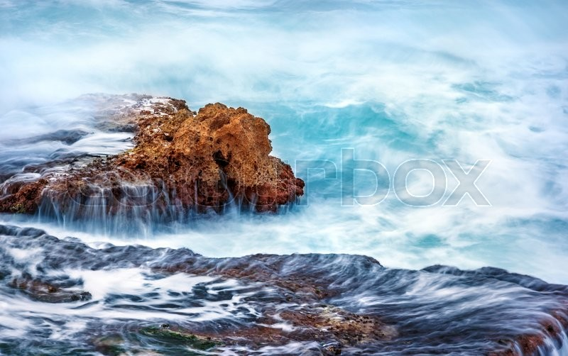 Beautiful rock in the sea, turquoise water flows over cliff at stormy weather day, slow motion scene, beauty of mother nature , stock photo
