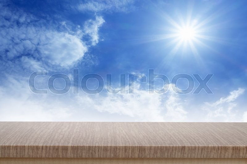Empty top of wooden table or counter and blured image of blue sky. For product display, stock photo