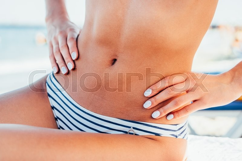 Slim tanned woman\'s body in a striped swimsuit on the beach, stock photo