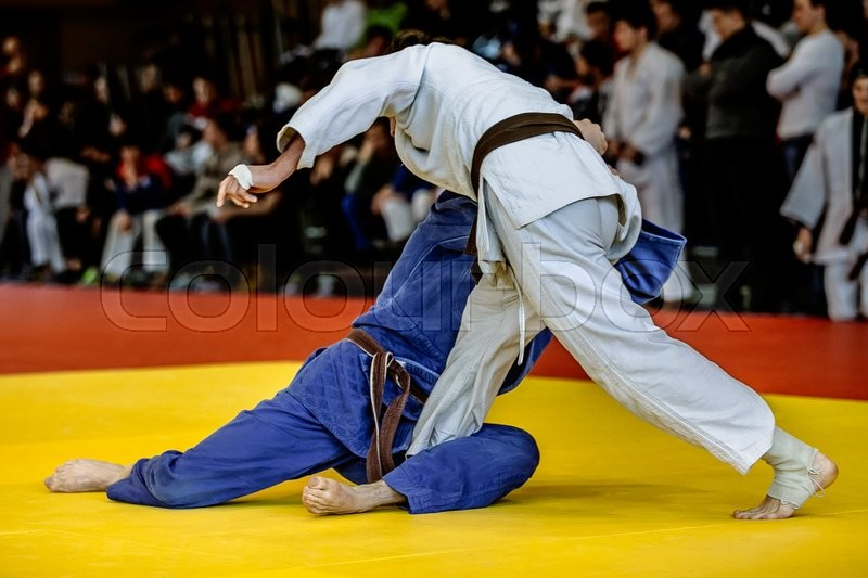 Fighters judoists fight in time to compete in judo on a tatami, stock photo