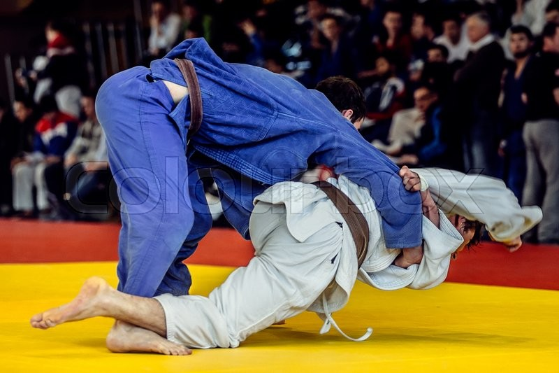Fighters judoists to compete in judo. in background fans, stock photo