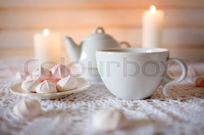 Tea time. Lunch with hot tea, candles and diet dessert white and pink marshmallows, stock photo
