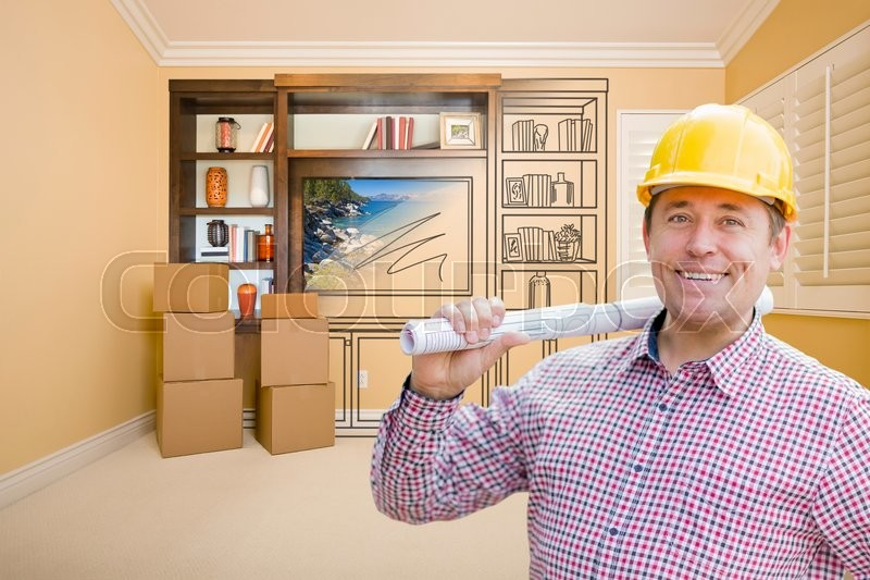Male Construction Worker Wearing Hard Hat In Room With Drawing of Entertainment Unit On Wall, stock photo