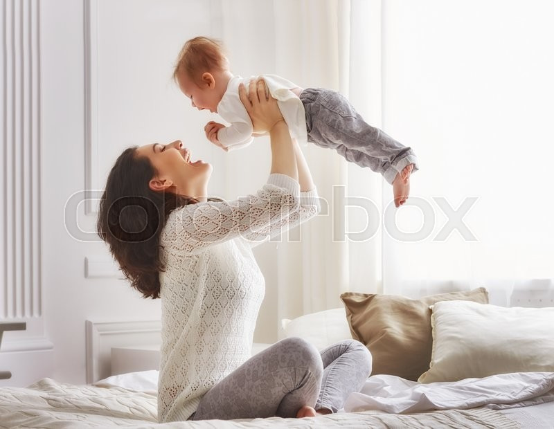 Happy loving family. mother playing with her baby in the bedroom, stock photo