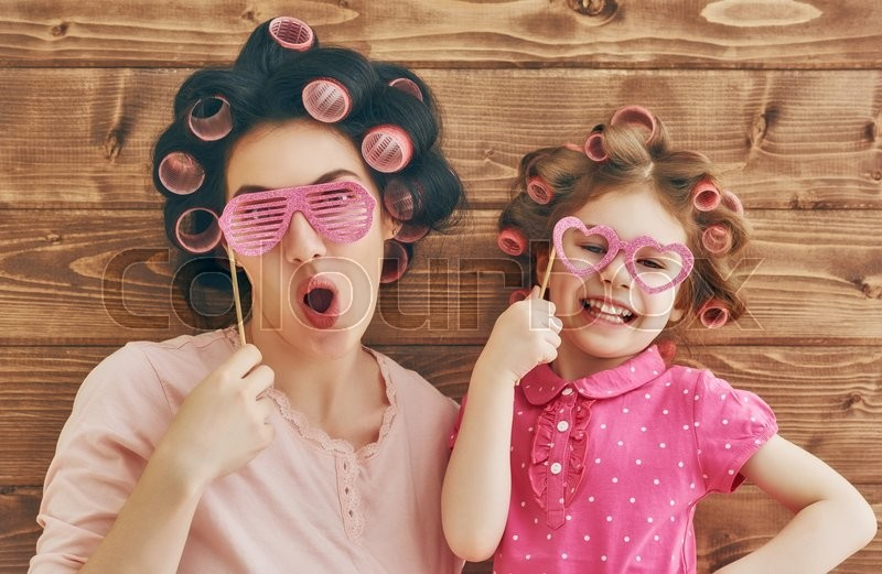 Funny family! Mother and her child daughter girl with a paper accessories. Beauty funny girl holding paper glasses on stick. Beautiful young woman holding paper glasses on stick, stock photo