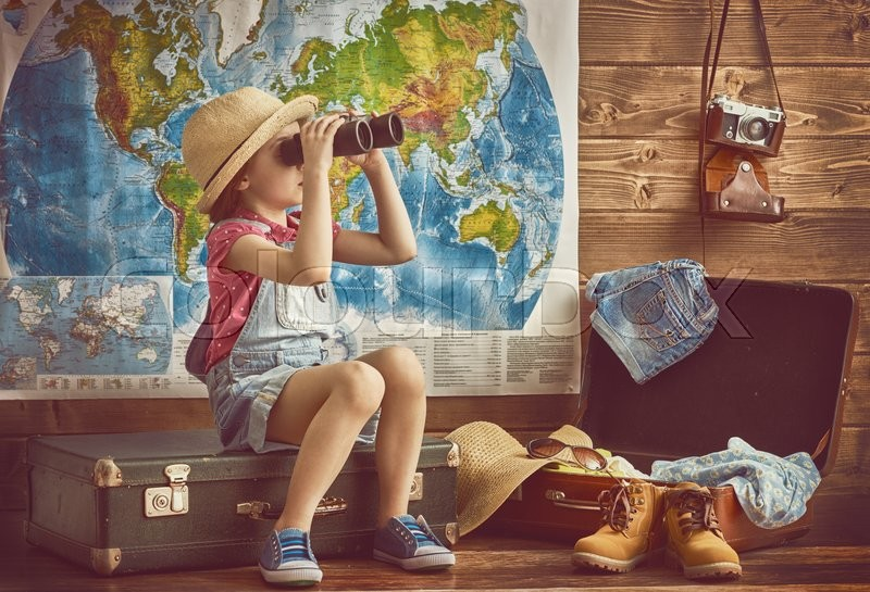 Happy baby girl getting ready for the journey. Girl packs her bags and playing with binoculars, stock photo