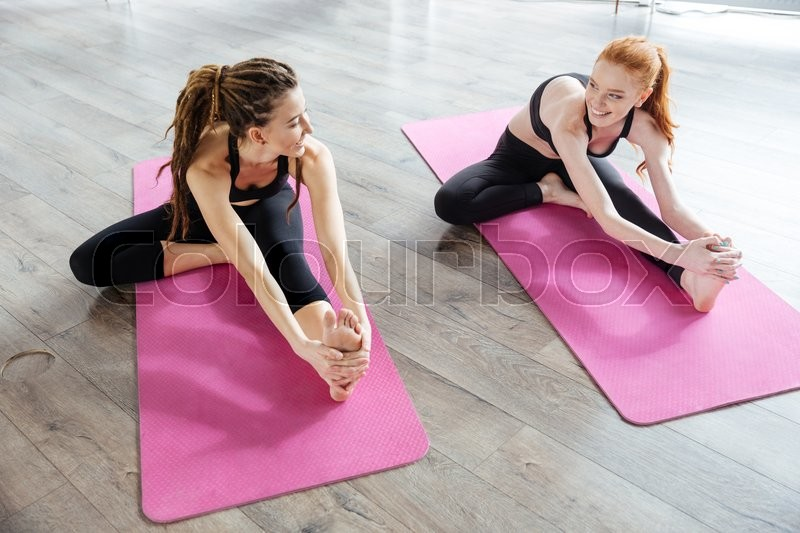 Two happy cute young women sitting and stretching in yoga center, stock photo
