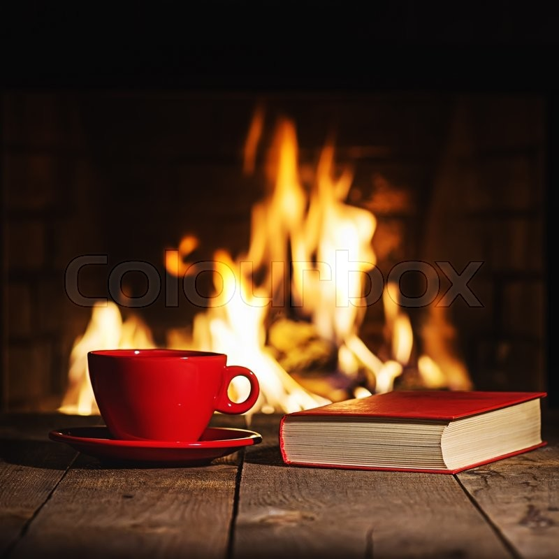 Red cup of coffee or tea and old book on wooden table near ...