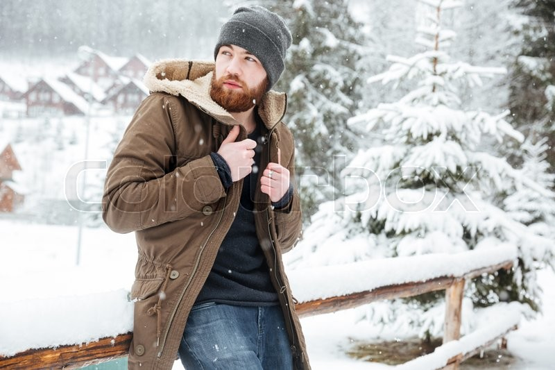 Attractive bearded man standing outdoors in wwnter, stock photo