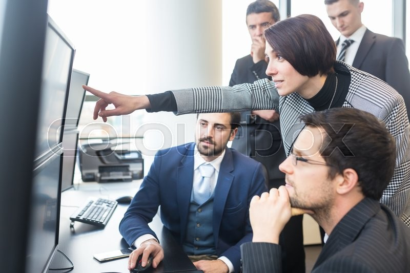 Business team looking at data on multiple computer screens in corporate office. Businesswoman pointing on screen. Business people trading online. Business, entrepreneurship and team work concept, stock photo
