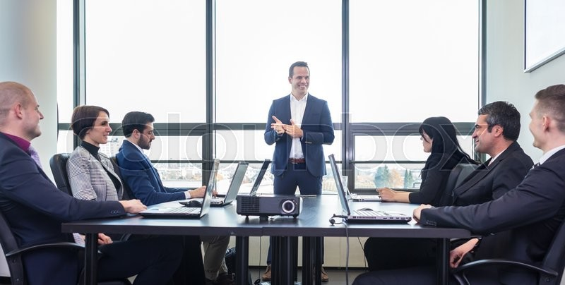 Successful team leader and business owner leading in-house business meeting, explaining business plans to his employees. Business and entrepreneurship concept, stock photo