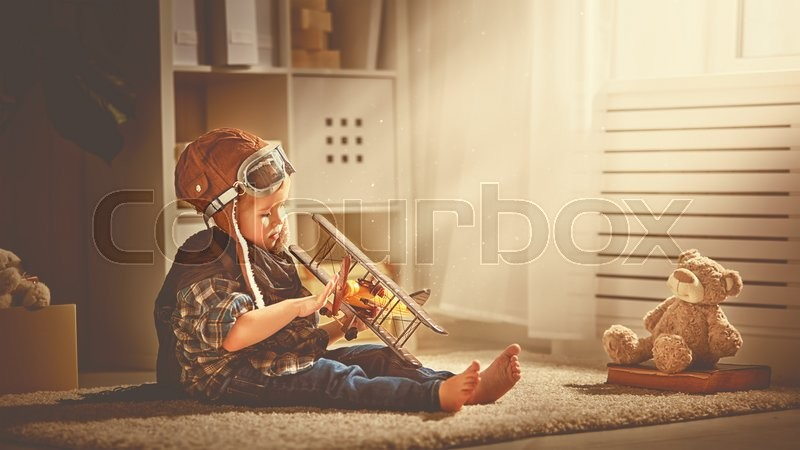 Concept of children\'s dreams and travels. pilot aviator child with a toy airplane plays at home in his room, stock photo
