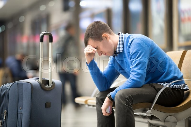 Portrait of young handsome guy wearing casual style clothes waiting for transport. Tired traveler man travelling with suitcase sitting with frustrated facial expression on a chair in modern station, stock photo