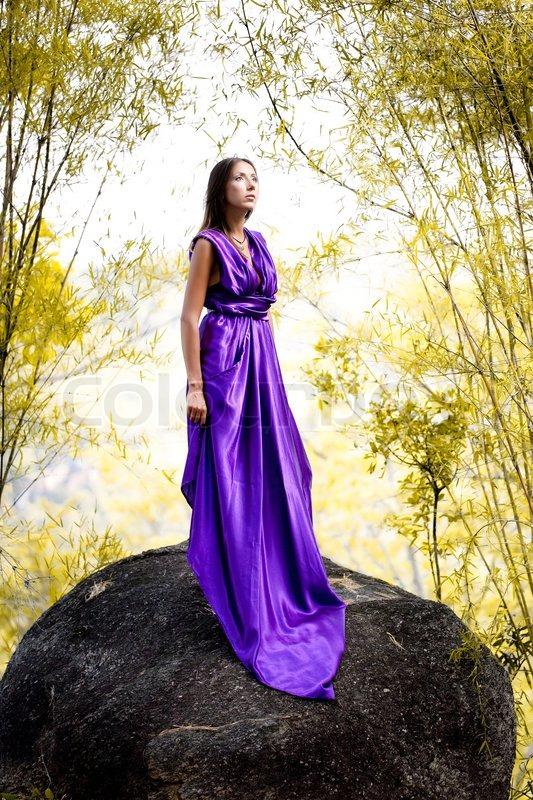 beautiful woman in lavendel langen kleid auf einem felsen. Black Bedroom Furniture Sets. Home Design Ideas