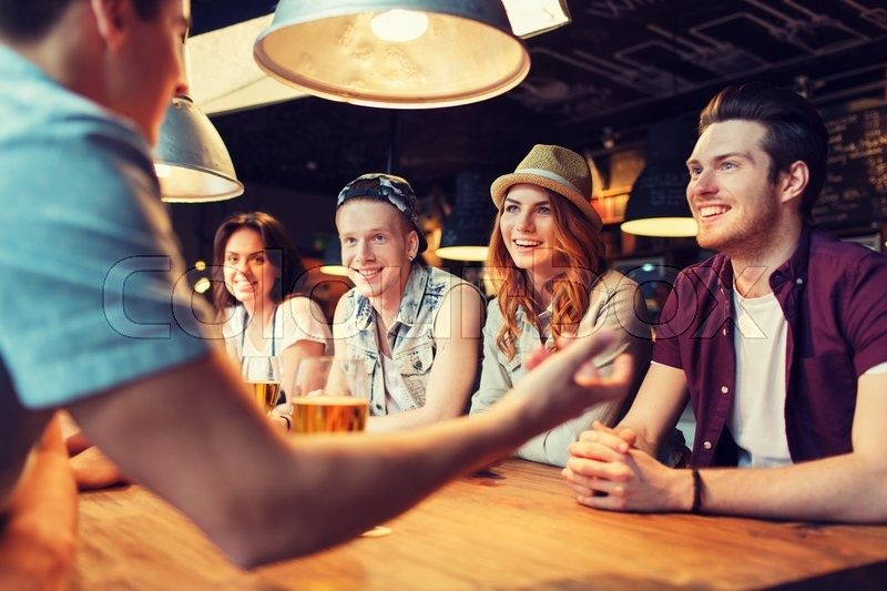 People, leisure, friendship and communication concept - group of happy smiling friends drinking beer and talking at bar or pub, stock photo