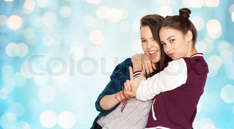 People, friends, teens and friendship concept - happy smiling pretty teenage girls hugging and showing peace hand sign over blue holidays lights background, stock photo