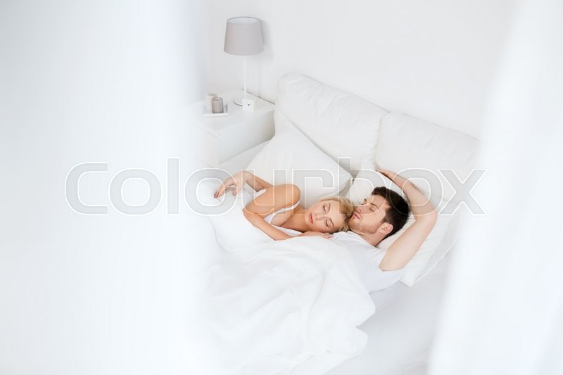 People, rest and relationships concept - happy couple sleeping in bed at home, stock photo