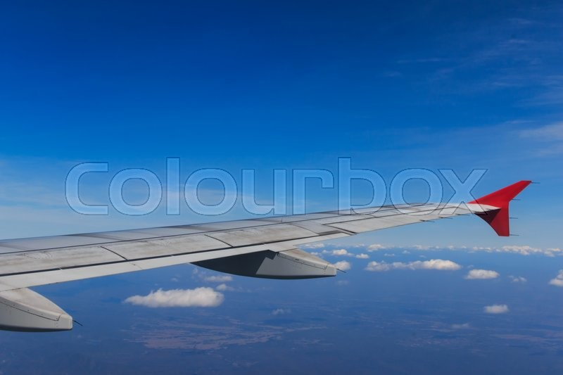 View of Beautiful Clouds sky and wing as seen through window of an aircraft, stock photo