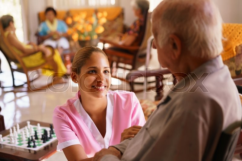 Old people in geriatric hospice: young attractive hispanic woman working as nurse takes care of a senior man on wheelchair. She talks with him then goes away to help other patients, stock photo