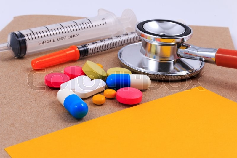 Red stethoscope, syringes, sticky note and many colorful pills on brown craft paper background, stock photo
