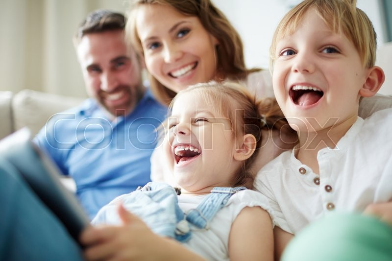 Children sitting together with parents and laughing, stock photo
