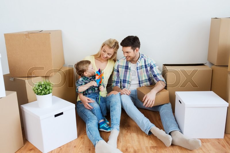 Mortgage, people, housing and real estate concept - happy family with boxes moving to new home, stock photo